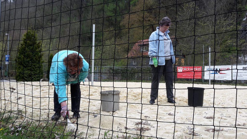 Der Sand im Volleyballfeld wird von Gras und Sämlingen befreit